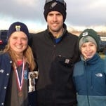 Senior Maddy Trevisan (left) and freshman Abby Inch (right) are pictured with Farmington co-coach Jeremy Auer.