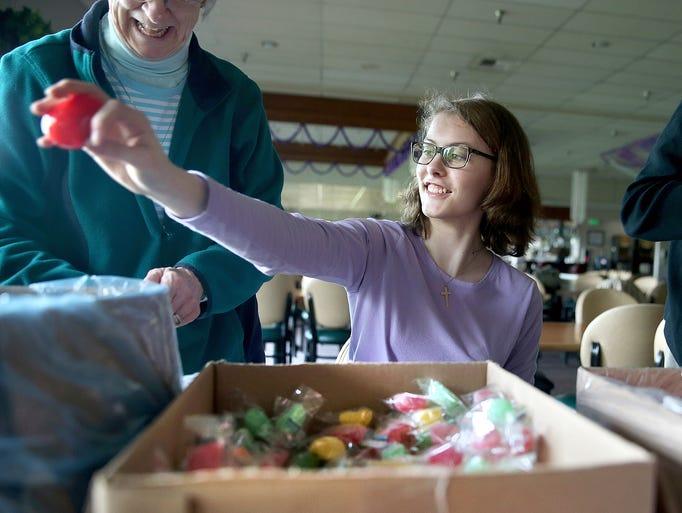Lydia Smithhisler finishes a plastic Easter egg filled