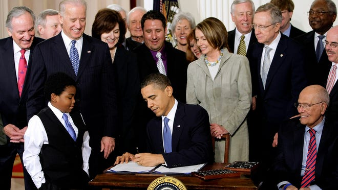 FILE - In this March 23, 2010 file photo President Barack Obama signs the health care bill in the East Room of the White House in Washington. He is flanked by Marcelas Owens of Seattle, left, and Rep. John Dingell, D-Mich. Behind, from left are, Sen. Tom Harkin, D-Iowa., Senate Majority Whip Richard Durbin of Ill., Vice President Joe Biden, Vicki Kennedy, widow of Sen. Ted Kennedy, Sen. Christopher Dodd, D-Conn., Rep. Sander Levin, D-Mich., Ryan Smith of Turlock, Calif., Health and Human Services Secretary Kathleen Sebelius, House Speaker Nancy Pelosi of Calif., House Majority Leader Steny Hoyer of Md., Senate Majority Leader Harry Reid of Nev., Rep. Patrick Kennedy, D-R.I., House Majority Whip James Clyburn of S.C., and Rep. Henry Waxman, D-Calif. The Supreme Court said Monday it will hear arguments in March over President Barack Obama?s health care overhaul, setting up an election-year showdown over the White House's main domestic policy achievement. (AP Photo/J. Scott Applewhite, File)