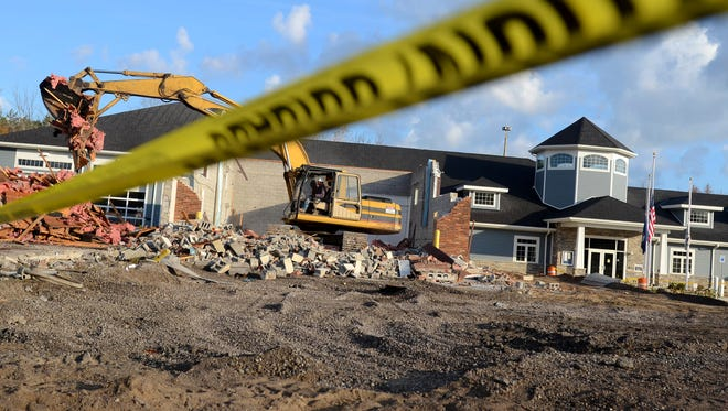 An excavator removes debris from the old fire truck bay Monday, Oct. 26, next to the new Fort Gratiot Township hall.