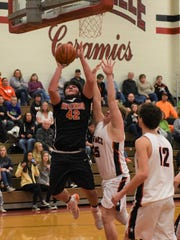 New Lex's Seth Russell takes a shot against Crooksville's Eric Taylor on Thursday. The Panthers won, 54-41.
