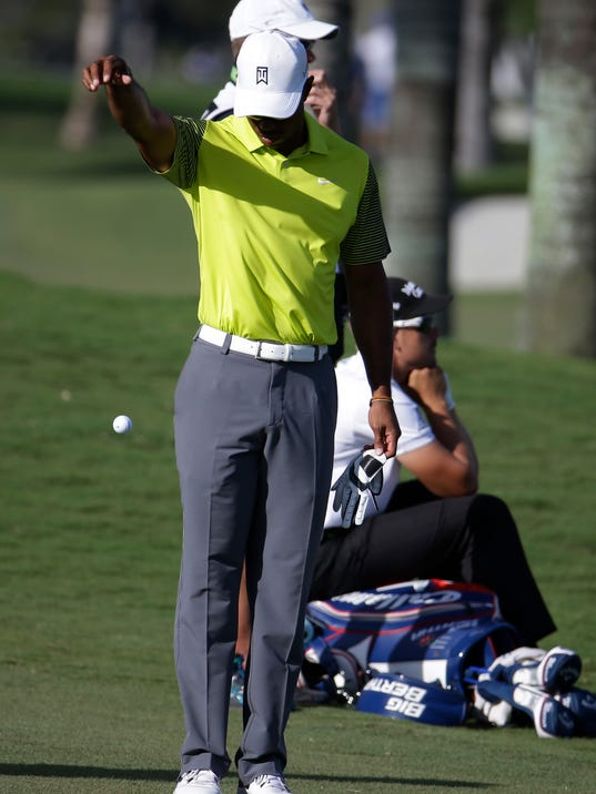 Tiger Woods takes a drop on the eighth hole during the second round of the Cadillac Championship golf tournament Friday, March 7, 2014, in Doral, Fla. More than 100 balls went into the water in the newly designed course. (AP Photo/Lynne Sladky)