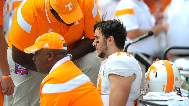 Tennessee quarterback Justin Worley (14) takes a break on the sidelines for a few plays after hurting his throwing arm as the University of Tennessee plays Georgia in Sanford Stadium  Saturday Sept. 27, 2014, in Athens, GA.