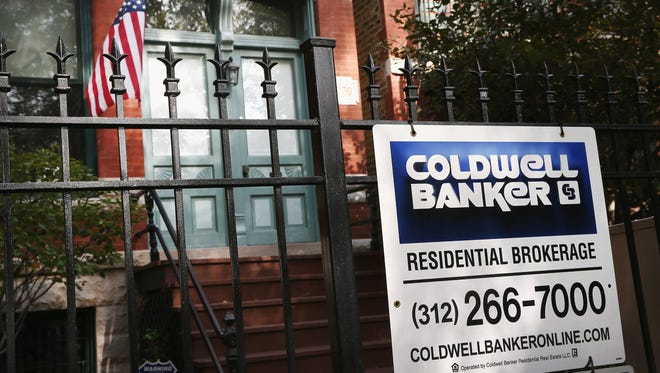 A real estate sign hangs on a fence in front of a home in the Wicker Park neighborhood  in Chicago. U.S. home prices are no longer showing the rapid monthly price gains they were earlier this year, according to CoreLogic, a real estate research firm.