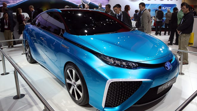 Attendees look at the Toyota FCV fuel cell vehicle concept car at the Toyota booth at the 2014 International CES at the Las Vegas Convention Center