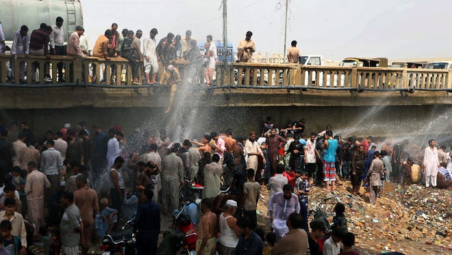 People attempt to cool off near a damaged water pipe in Karachi, Pakistan, on June 25, 2015. More than 1,000 people have died in Pakistan's worst heat wave on record.