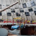 Kimberly, left, and David Tompkins lean over to take a look at the sinkhole during a visit to the National Corvette Museum on Saturday, Aug. 30, 2014, in Bowling Green, Ky. (AP Photo/The Daily News, Miranda Pederson)