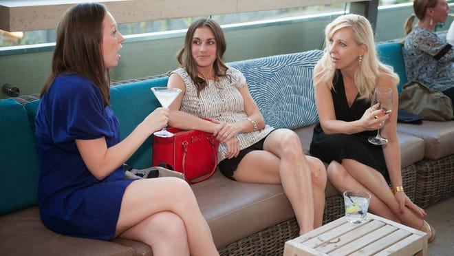 """Christine Woolley (from left), 28, and Callye Emmons, 29, speak with publicist Ania Kubicki at the Phoenix area's first """"egg-freezing party"""" held at Del Frisco's Grille in April 2015."""