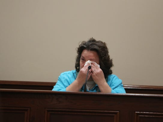 Kelley Hufford wipes her eyes while testifying about