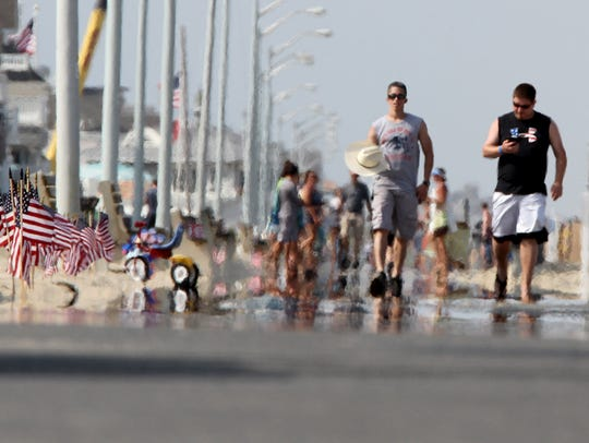 Heat rises from the Manasquan boardwalk as people stroll