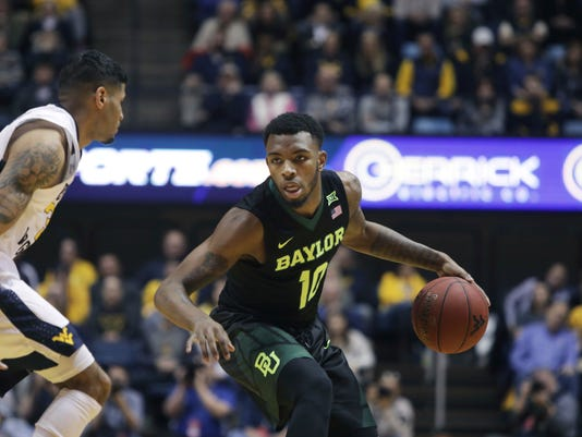 Baylor guard Tyson Jolly (10) drives up court while being defended by West Virginia guard James Bolden (3) during the first half of an NCAA college basketball game Tuesday, Jan. 9, 2018, in Morgantown, W.Va. (AP Photo/Raymond Thompson)
