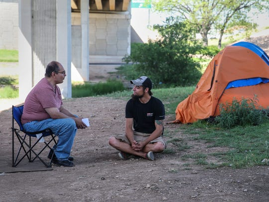 Standard-Times reporter Federico Martinez talks with Dustin Halvorson at the tent city under the Houston Harte Expressway in San Angelo.