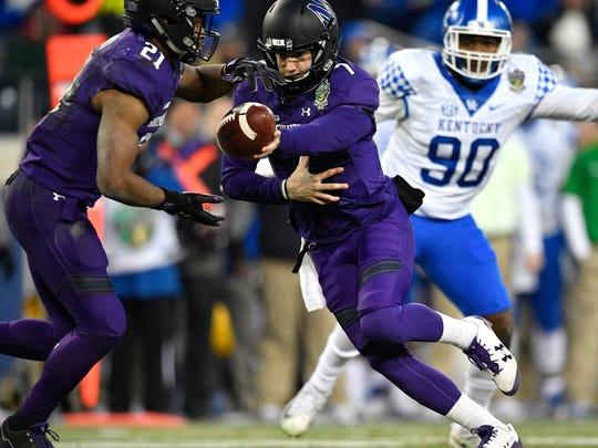 Northwestern quarterback Matt Alviti (7) in for the injured quarterback Clayton Thorson (18) hands off to running back Justin Jackson (21) during the first half of the Music City Bowl at Nissan Stadium in Nashville, Tenn., Friday, Dec. 29, 2017.
