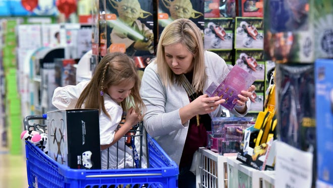 FILE - In this Thursday, Nov. 24, 2016, file photo, Stephanie Rowell and her daughter Sydney, 5, shop at Toys R Us - Town Center in Kennesaw, Ga. Holiday shopping procrastinators can breathe easy. Yes, most online shipping deadlines have passed. But many retailers are offering other ways to get gifts at the last minute, whether it's staying open through the wee hours of the night like Toys R Us, or offering Christmas Eve store pickup like Wal-Mart.