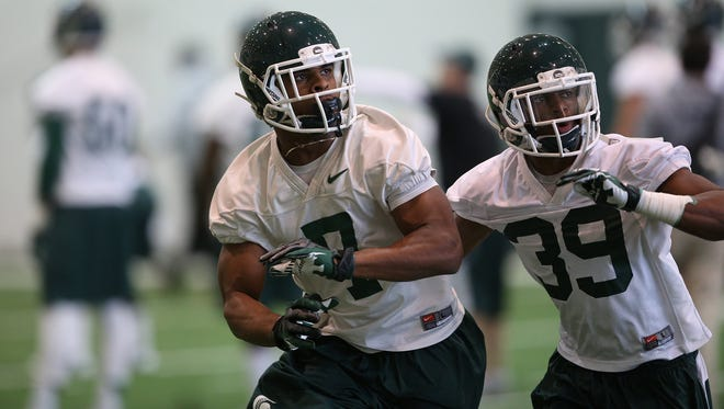 Michigan State University cornerback Jermaine Edmondson defends as safety Demetrious Cox runs a drill during a spring football practice.