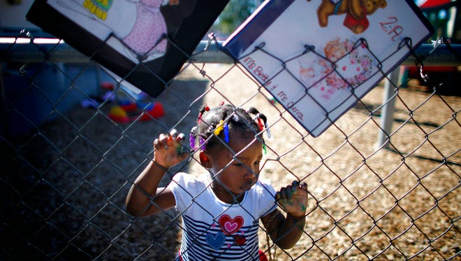 It was a simple, quick photo, grabbed in a few milliseconds as I walked out onto the playground.  I held my breath and clicked off three or four frames of Dannia Jean-Louis, hoping she wouldn't react to a 6-foot something stranger shoving a camera in her face. She headed back to her finger painting, never once taking notice of me. The little girl aligned by light and composure, a fleeting moment as she looked over to the other side of the fence and big kids playing big games.    Dannia Jean-Louis had poked her fingers through the fence during outdoor time at the Immokalee Child Care Center.  Dipped in red, green and blue, they match her colorful hair braids, a result of the masterpiece she's created in tempra paint and white paper.    Without words, she seemed to be saying the grass was indeed greener on the other side and frustrated, she headed back to her project. She was, of course, in the right place.  At two, she's too young to play with the older kids and her exposure to art and music are an integral part of the child care center's education program that will help her grow into that healthy big kid.    For the working poor, quality day care can be elusive, even unobtainable.  One of approximately 100 enrolled, she's one of the fortunate, a student at a quality day care and learning facility in a community struggling to meet the needs of it's citizens.  Michel Fortier/Staff mjfortier@naplesnews.com