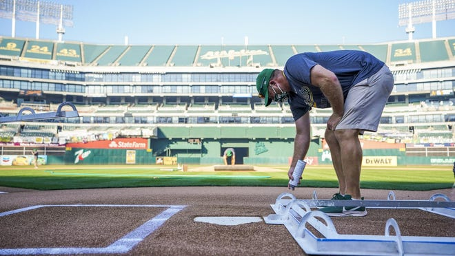 Zach Ricketts, a 2007 Galesburg High School grad and an assistant head groundskeeper for the Oakland Athletics, paints the lines for the batters box before a Major League Baseball game between the A's and Arizona Diamondbacks on  Wednesday, Aug. 19, in Oakland, Calif.