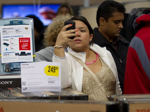 A shopper uses her smart phone to shop for bargains at the Pembroke Pines, Fla. Best Buy, Nov. 22, 2012.