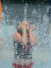 Sophia Castelli is nearly lost in a shower of cooling water during a July 6 visit to Kensington Metropark's Splash n' Blast.