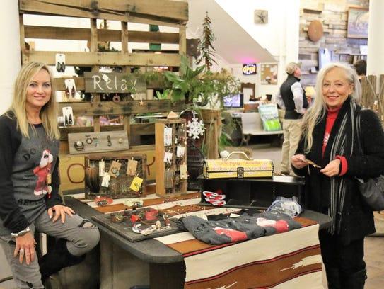Artist Tammy Askew shows her jewelry to customer Gina
