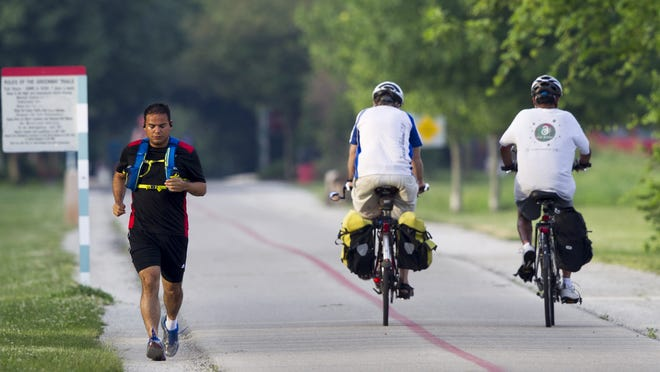 Indianapolis resident Oscar Clavel, who says he's lost 40 pounds since November, used the early-morning hours to get in a 40-minute run in Tuesday on  the Monon Trail in Indianapolis.