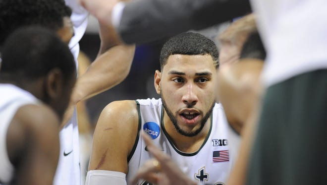 MSU's Denzel Valentine, center, and the rest of the Spartans listen to head coach Tom Izzo in the huddle during a timeout against Georgia during their NCAA tournament game Friday in Charlotte, N.C.