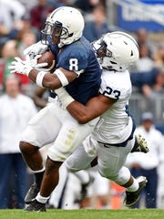 Senior Mark Allen (8) ran hard and effective again in a starring role in the Blue-White Game. Here, he was tackled in last year's scrimmage by Ayron Monroe. This time, he scored a first-half touchdown for the Blue team.
