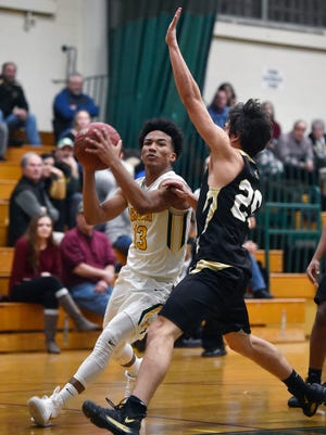 York Catholic's D'Andre Davis drives against Delone Catholic's Evan Brady in the second half of a YAIAA boys basketball game Friday, Jan. 5, 2018, at York Catholic. York Catholic defeated Delone Catholic 70-36.