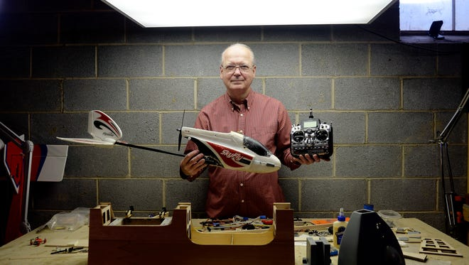 Paul Marsh stands for a portrait with a model airplane whose circuit boards allow it to fly on autopilot and with his handset controls in his Lower Windsor Township home. Marsh, who builds and flies amateur drones with and without cameras, said he understands why the FAA is starting to consider a system that would register unmanned aerial vehicles such as drones and model airplanes.