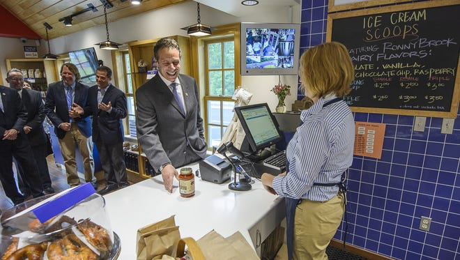 Gov. Andrew Cuomo purchases a jar of marinara sauce produced by McEnroe Organic Farm in Millerton at the 2014 opening of the Taste NY Market at Todd Hill, on the Taconic State Parkway in LaGrangeville.