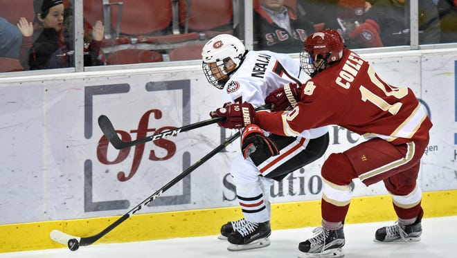 St. Cloud State's Niklas Nevalainen and Kevin Conley of Denver try to control the puck along the boards during the first period of the Friday, Jan. 20, game at the Herb Brooks National Hockey Center in St. Cloud.