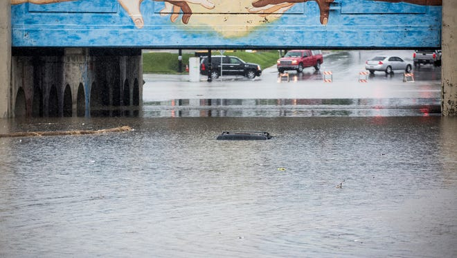 An SUV is submerged under flood water near the Madison Street underpass after heavy rain in June.