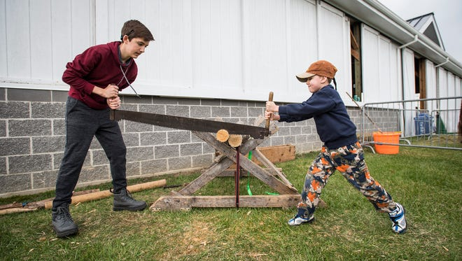 Jeffrey Baker, 14, left, saws through a piece of wood with his brother Joziah, 7, both of Smith's Creek, at one of the exhibits at Earth Fairy, held Friday, April 27 at Goodells County Park.
