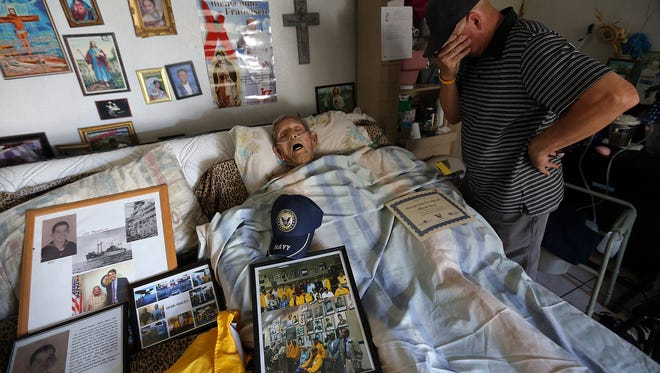 World War II veteran Alfredo Gomez, 92, lies in the bed of his home where he had lived for 88 years as his son, Tony Gomez, arrives to join family members in saying goodbye. He died soon after this moment. He was off the coast of Japan when the atomic bombs were dropped and witnessed the signing of the Japanese Instrument of Surrender.
