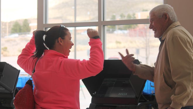 Gene Dennis, volunteer, helps a resident submit her ballot for the special school bond election on Tuesday morning.
