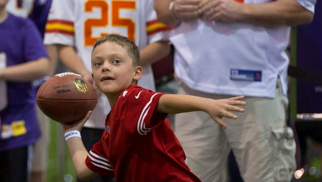 Nicolas Gonzales, 7, throws a football at one of the many skills games during the NFL Experience at the Phoenix Convention Center on Jan. 24, 2015.