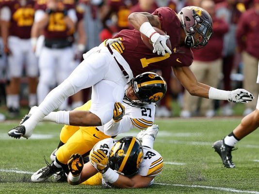 Minnesota running back Rodney Smith (1) is brought down by Iowa defensive back Amani Hooker (27) and linebacker Jack Hockaday (48) during an NCAA college football game Saturday, Oct. 8, 2016, in Minneapolis. (AP Photo/Stacy Bengs)