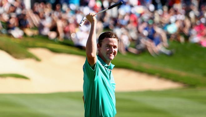 Jimmy Walker celebrates after making his putt on the 18th hole to win the final round of the Valero Texas Open.
