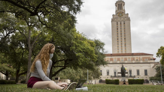 Maggie Quinn, 19, watches a geography class online while sitting on the South Mall at the University of Texas on Aug. 26, the first day of the fall semester.