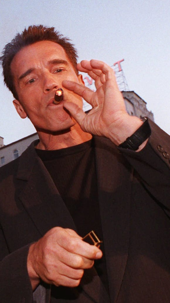Arnold Schwarzenegger lights up a cigar in 1996.