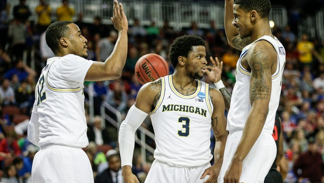 Michigan's Muhammad-Ali Abdur-Rahkman (12), Zavier Simpson (3) and Charles Matthews (1) celebrate a play against Houston on Saturday.