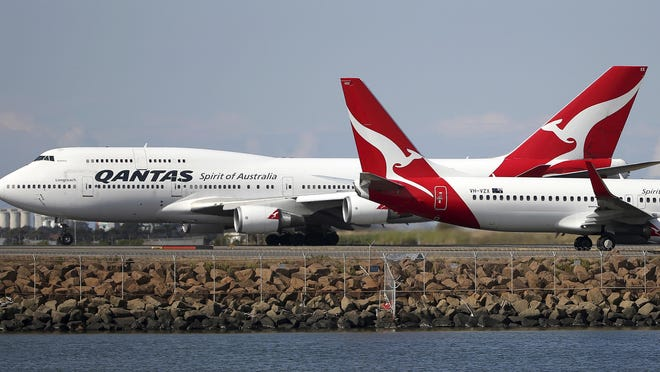 FILE - In this Aug. 20, 2015 file photo, two Qantas planes taxi on the runway at Sydney Airport in Sydney, Australia. Some Asian airlines have rerouted flights to the Middle East to avoid Iranian airspace, amid escalated tensions over the United States' assassination of a prominent Iranian commander in Iraq. (AP Photo/Rick Rycroft, File)