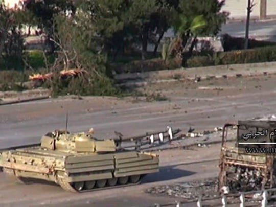 This frame grab from video provided by the government-controlled Syrian Central Military Media, shows a tank of Syrian troops passing by the remains of a burned bus, in an eastern neighborhood of Damascus, Syria, Wednesday, March. 22, 2017. Syrian troop are engaged in fighting with insurgents who have tried to breach government lines in eastern neighborhoods of the capital this week. The operation is spearheaded by the al-Qaida-linked Levant Liberation Committee.