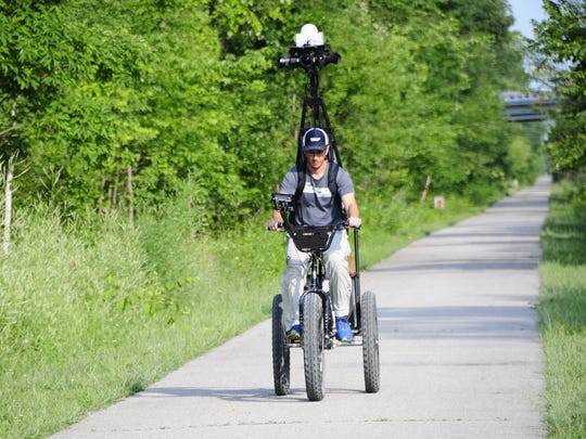 Andy Thompson rides a large tricycle to map the Wadhams to Avoca Trail.