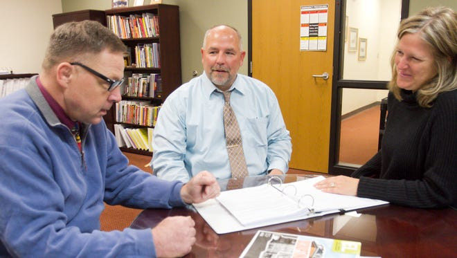Newly appointed Hartland Schools superintendent Chuck Hughes, center, talks with legacy team members Bill Cain, principal at Village Elementary, and Michelle Otis, community education director in a meeting in his office.