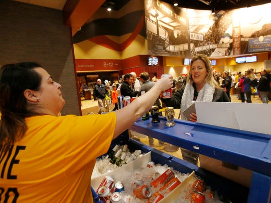 """Heather Barkley, of Smyrna, hands over a Bud to Kristi Wallace, of Middletown, who was at Westown Movies in Middletown to see """"Fifty Shades of Grey."""" The theater started selling alcohol in February."""