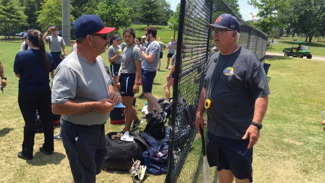 UA coach Mike Candrea meets Auburn coach Clint Myers before Friday's workout. Myers coached at Arizona State from 2006-13.