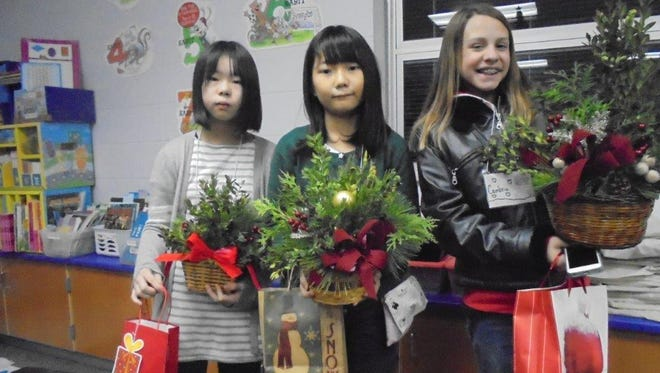 Three of the Peas-in-a-Pod  juniors gardeners are ready to leave the December meeting, holding the basket designs made during the meeting and a Robber's Bingo gift  selected during a game. (L to R) Haruka Nishimura, Kaho Miyake. and Cambria Wolff. This meeting was part of the busy week in the columnist's season