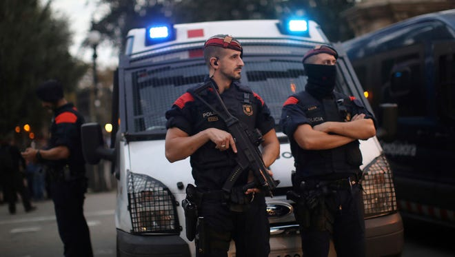 Spanish police officers stand guard at the entrance to the Parliament of Catalonia in Barcelona, Spain, on Oct. 10.