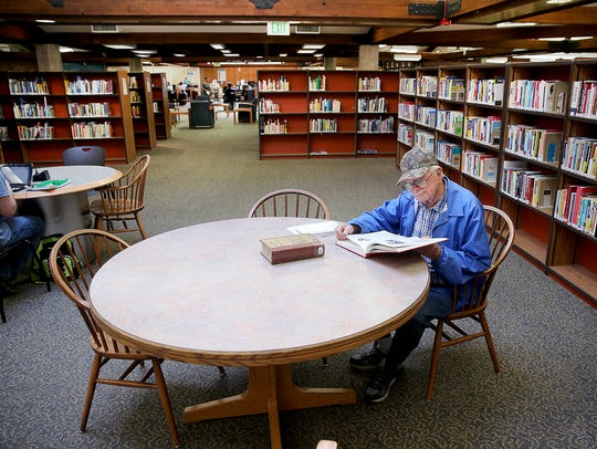 Paul Moses performs research at the East Bremerton branch of the Kitsap Regional Library on Monday. If voters approve a levy increase, the library system plans to buy new furniture, among other things.
